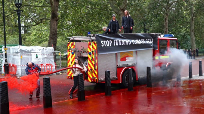 Protesters spray fake blood from a fire engine